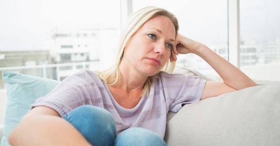Sad woman, sitting on her couch © iStock