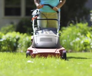Woman mowing grass with electric mower