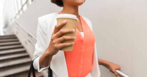 Woman on stairs holding coffee | Syda Productions/Shutterstock.com