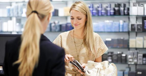 Woman paying in register of cosmetics store