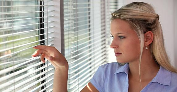 Woman peering through window blinds © auremar/Shutterstock.com