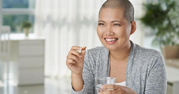 Smiling woman with shaved head taking a pill © Dragon Images/Shutterstock.com