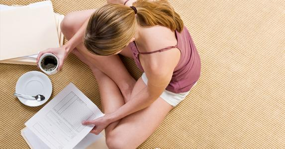 Woman sitting on floor, reading paperworks at home © iStock