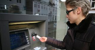 Woman taking cash from outdoor ATM © jean schweitzer/Shutterstock.com