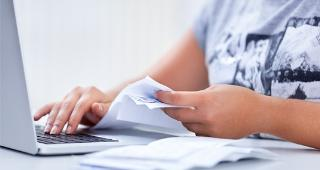 Woman doing paperwork on laptop © Singkham/Shutterstock.com