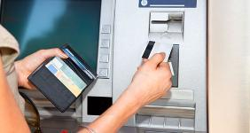 Woman using debit card at ATM machine  Aleksandar Todorovic / Shutterstock.com