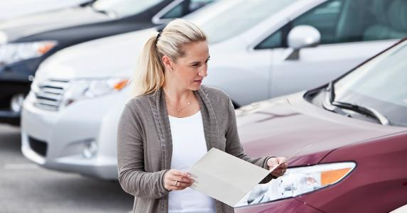 Woman walking along car lot © iStock