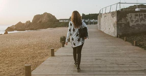 Woman walking along pier | Sandra Chile/Unsplash