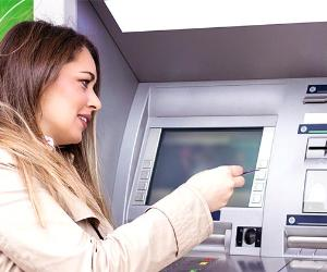 Woman withdrawing from ATM | pecaphoto77/Getty Images