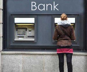 Woman withdrawing from ATM outside bank © Capricorn Studio/Shutterstock.com