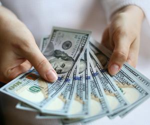 Woman's hands holding money © PavelIvanov/Shutterstock.com