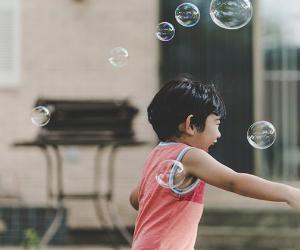 Young boy playing with bubbles in home's backyard | David Schlap/Unsplash