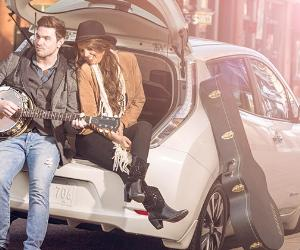 Young couple sitting at back of 2015 Nissan Leaf | Nissan
