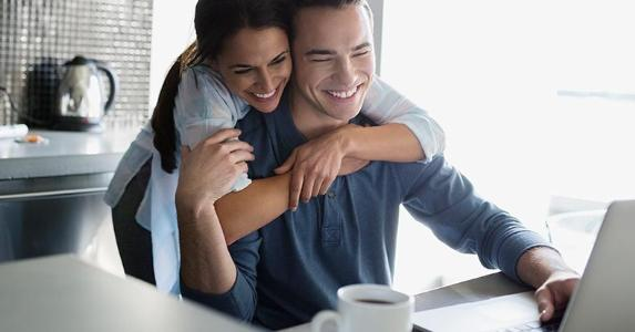 Young couple hugging in kitchen | Hero Images/Getty Images