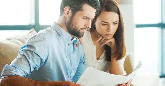 Young couple overlooking paperwork © g-stockstudio Shutterstock.com