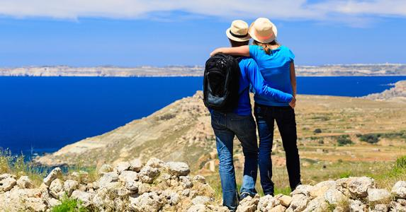Young couple looking at scenic view from the mountains © iStock