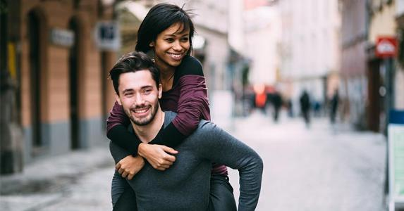 Young man giving woman piggyback ride | Peter Bernik/Shutterstock.com