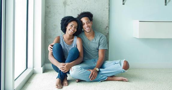 Young couple sitting on carpeted floor | Gary John Norman/DigitalVision/Getty Images