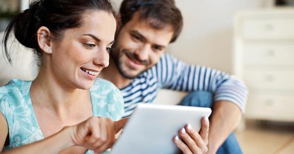 Young couple sitting on floor browing on tablet © iStock