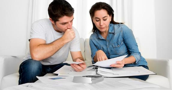Young couple worried sorting bills, paperwork