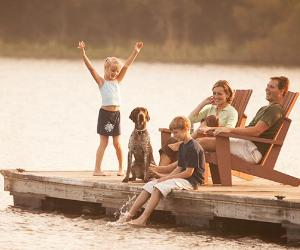 Young family and dog sitting on deck by the river | JonFeingersh/Getty Images