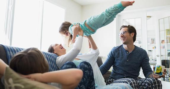 Young family wearing pajamas playing in living room | Hero Images/Getty Images