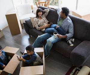 Young family lounging in new house's living room | Hero Images/Getty Images