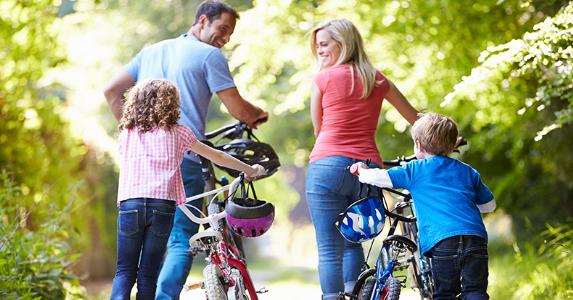 Young family pushing bikes along country track