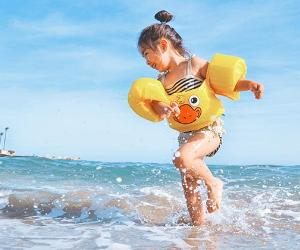 Young girl playing in the ocean water | Leo Rivas-Micoud/Snapstock