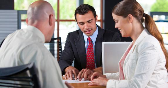 Adviser reviewing paperwork with clients © iStock