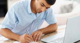 Young man writing notes at desk © Yuri Arcurs - Fotolia.com