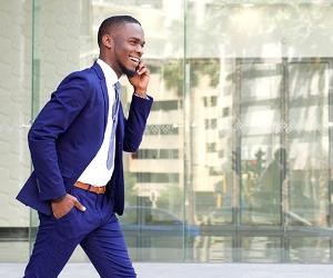 Young man in blue suit walking while talking on phone © mimagephotography/Shutterstock.com