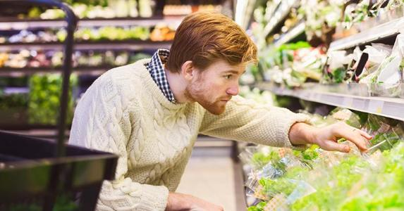 Young man buying produce in grocery store   Maskot/Getty Images