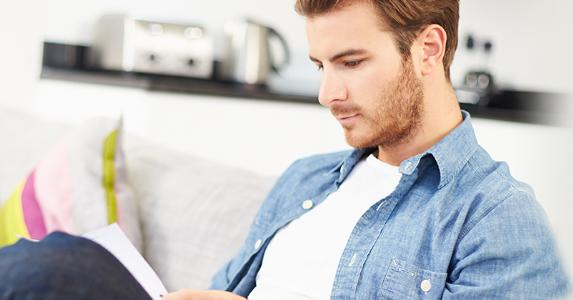 Young man looking through personal finances at home © Monkey Business Images/Shutterstock.com