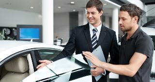 Car salesman in showroom © LifePhotoStudio/Shutterstock.com