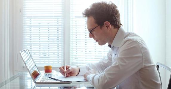 young-man-working-at-home-table-laptop-notebook-dressed_573x300