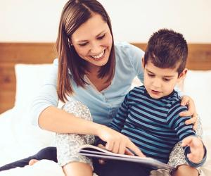 Young mom reading bedtime story to son © iStock