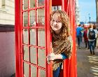 Young woman in red phone booth in London | Tom Bonaventure/Getty Images