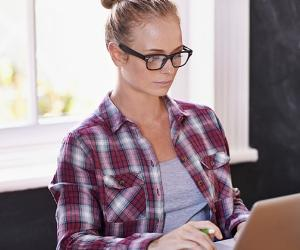 Young woman on red flannel shirt using laptop