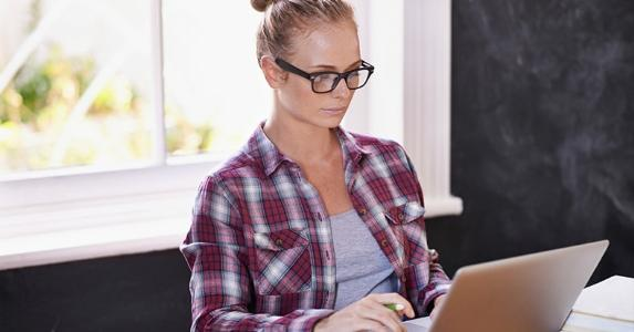 Young woman on red flannel shirt using laptop | iStock.com