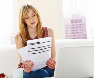 Young woman reading documents, working on finances at home © iStock