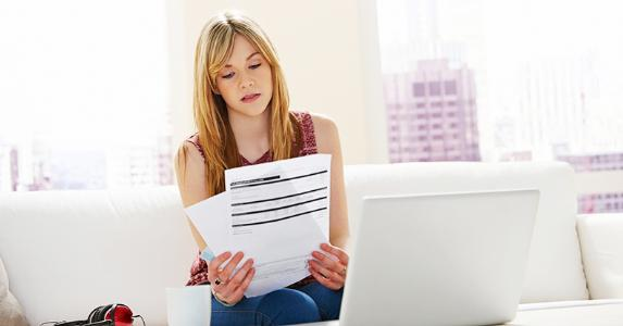 Young woman reading documents, working on finances at home