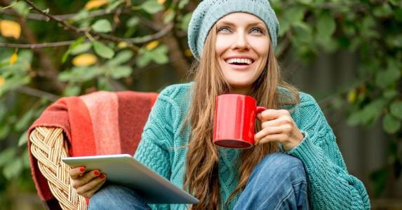 Young woman sitting with tablet and coffee mug © PEPPERSMINT/Shutterstock.com