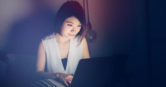 Young woman using notebook computer in dark room | Oscar Wong/Moment/Getty Images
