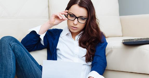 Young woman wearing glasses and reading paperwork © baranq/Shutterstock.com