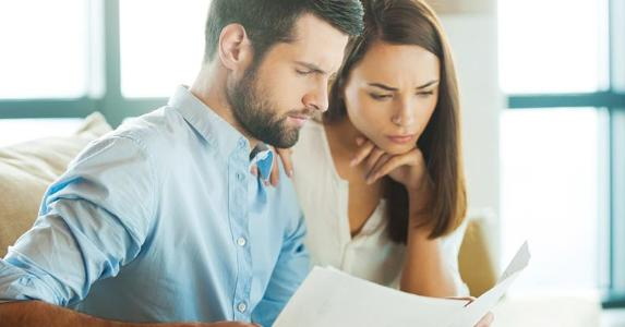 Younger couple looking over paperwork together | iStock.com